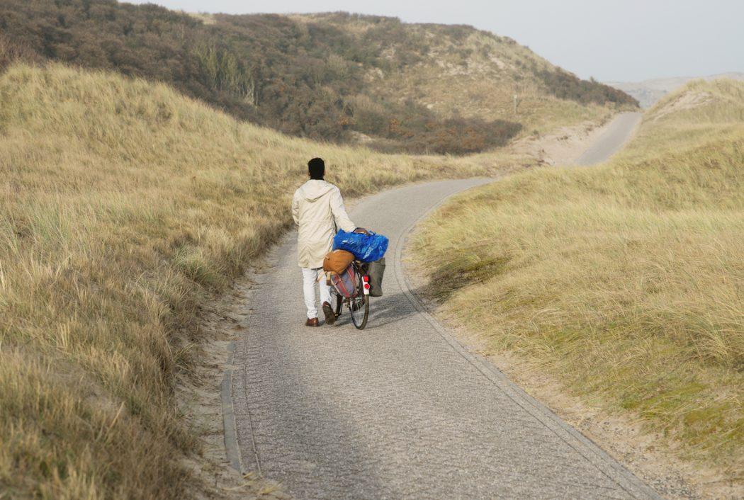 Jongen met bepakte fiets in de duinen